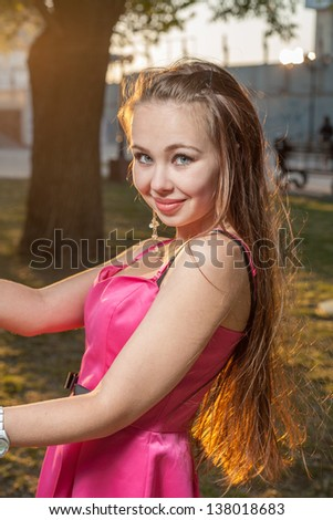 Beautiful woman pink dress in a park outdoor backlit by sunlight near tree - stock photo