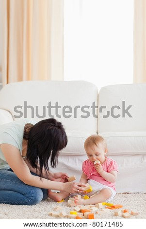 Beautiful woman playing with her baby in while sitting on a carpet in the living room - stock photo