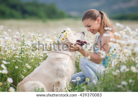 Beautiful woman playing with her golden retriever pet dog. Outdoor portrait. chamomille field. Young woman with ger dog resting at green field - stock photo