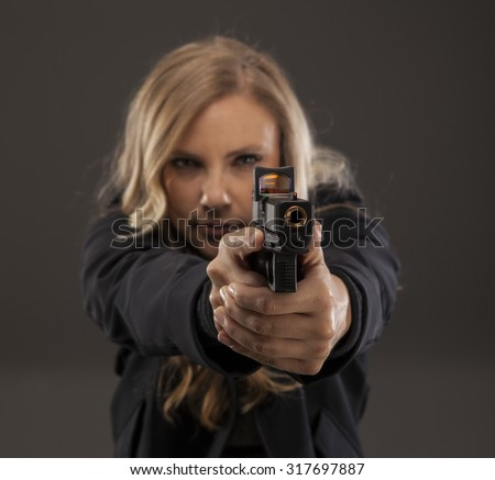 Beautiful woman pointing and aiming a gun. REFUSE TO BE A VICTIM. - stock photo