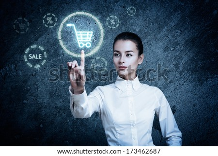 Beautiful Woman Pointing at Glowing Shopping Cart Icon. Perfect Online Shopping Business Concept - stock photo