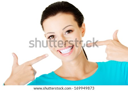 Beautiful woman pointing on her perfect white teeth. Isolated on white. - stock photo
