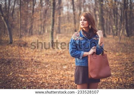 Beautiful woman portrait in a romantic autumn fall scenery wearing a denim jacket with geometric print. Fashion female ready for shopping - stock photo