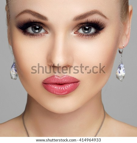 Beautiful woman portrait isolated on grey background. Young woman with full lips, long eyelashes, clear skin, makeup. - stock photo