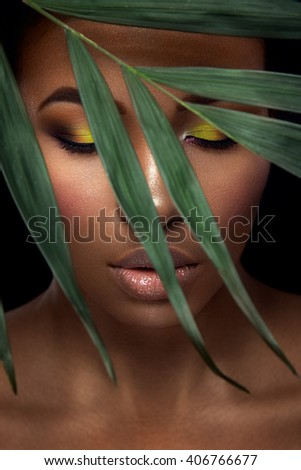 Beautiful woman portrait on black background. Young afro girl posing with green leaves and  closed eyes. Gorgeous make up. Pure skin - stock photo