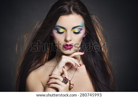 Beautiful woman portrait with bright colorful makeup - stock photo