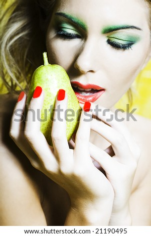 beautiful woman portrait with colorful make-up  and background holding pear - stock photo
