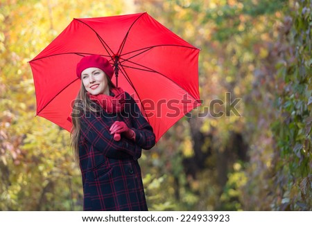 Beautiful woman portrait with red umbrella over yellow autumn background - stock photo