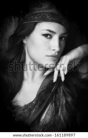 beautiful woman portrait with scarf black and white small amount of grain added - stock photo