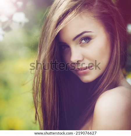 Beautiful woman portrait. Young cheerful girl with long brown hair and clean skin. Outdoor close up portrait - stock photo