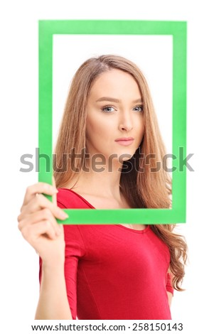Beautiful woman posing and holding a green picture frame in front of her face isolated on white background - stock photo