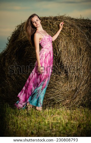 Beautiful woman posing at the old rural farm location. Outdoor summer portrait of pretty fashion style woman in colored dress over haystack.  Sexy slim model caucasian ethnicity outdoors. - stock photo