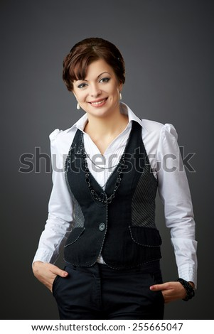 Beautiful woman posing in a studio in stylish clothing on a gray background - stock photo