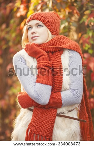 beautiful woman posing in red knitwear against colorful grape leaves - stock photo