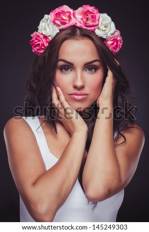 Beautiful woman posing in the studio with flower hairband on her head - stock photo