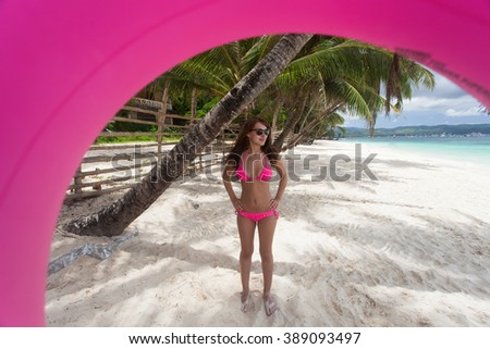 Beautiful woman posing with float tube on the beach - stock photo
