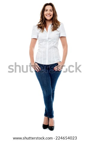 Beautiful woman posing with hands in pockets, legs crossed - stock photo