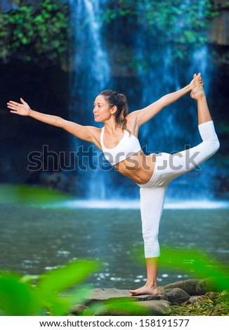 Beautiful Woman Practacing Yoga in Nature, Beautiful Natural Waterfall  - stock photo