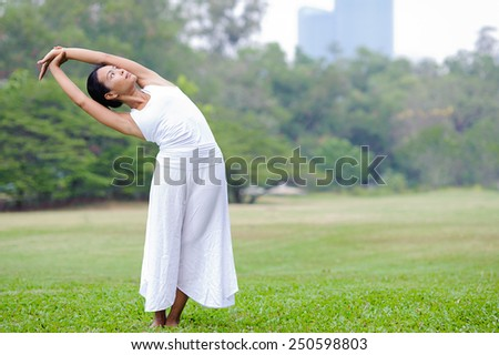 Beautiful woman practicing yoga in the park.Half Moon Pose / Ardha Chandrasana - stock photo