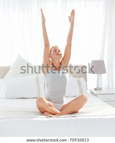 Beautiful woman practicing yoga on her bed at home - stock photo