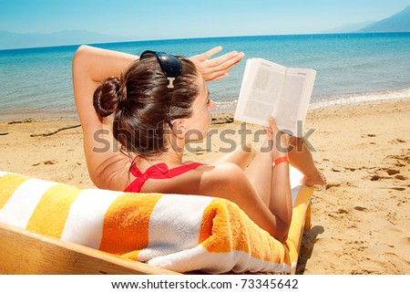 beautiful woman reading a book on background of beach - stock photo