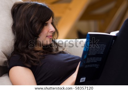 beautiful woman reading a book on the couch - stock photo