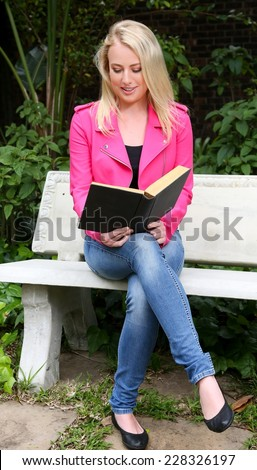 Beautiful woman reading a book outdoors while sitting on a concrete bench - stock photo