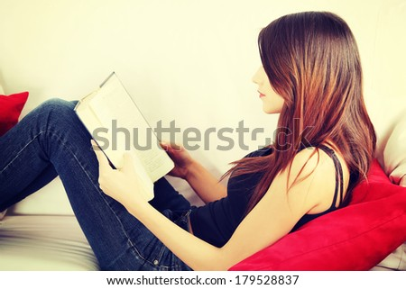 Beautiful woman reading a book, sitting on a sofa in a living-room  - stock photo