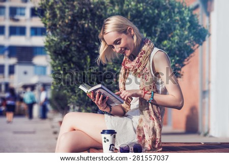 beautiful woman reading a book smiling - stock photo