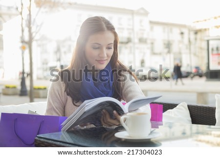 Beautiful woman reading book at sidewalk cafe - stock photo