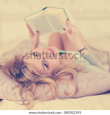 Beautiful woman reading on a bed relaxing turning to give the camera a beaming smile. Instagram style filtred image  - stock photo
