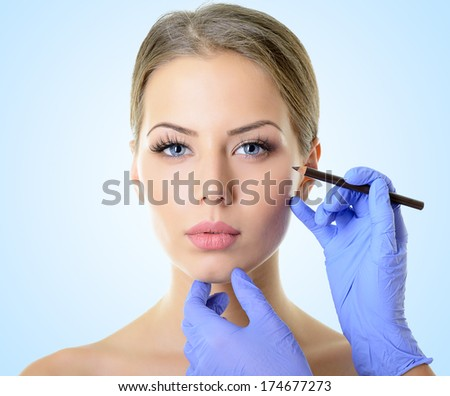 Beautiful woman ready for cosmetic surgery, female face with doctor's hands with pencil, over blue - stock photo