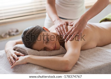 Beautiful woman receiving a relaxing back massage at spa. - stock photo