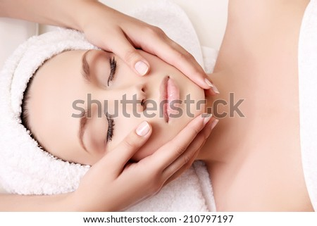 Beautiful woman receiving facial massage and spa treatment - stock photo