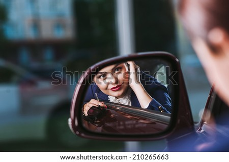beautiful woman reflected in mirror of car - stock photo