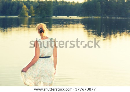 Beautiful woman refreshing herself in the water of a lake and raises her sundress up so it does not get wet. Wonderful summer atmosphere, Nordic Light. Vintage style, in the colors of an old picture.  - stock photo