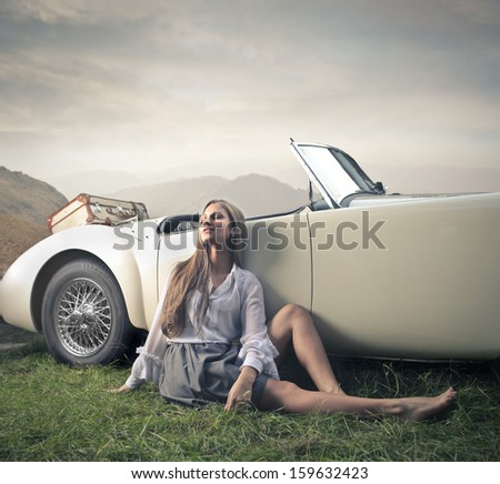 beautiful woman relaxes leaning against a vintage car - stock photo