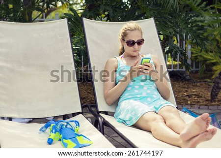 Beautiful woman relaxing and checking her cell phone - stock photo