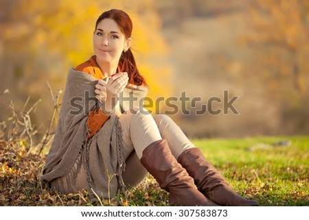 Beautiful woman relaxing and drinking coffee, sitting in autumn garden, wrapped in a blanket wool blanket. - stock photo