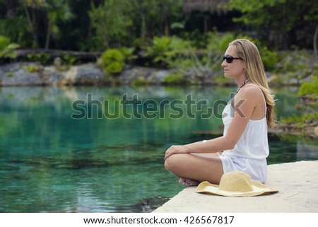 Beautiful woman relaxing and meditating in a jungle pool at a tropical island resort - stock photo
