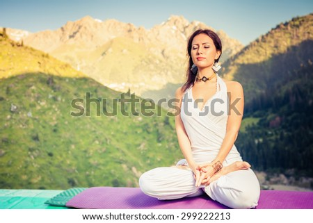 Beautiful woman relaxing and meditating outdoor at swiss mountain. She sits at peak of mountain in lotus position and feel harmony of your body and nature. Healthy lifestyles concept of body and soul - stock photo