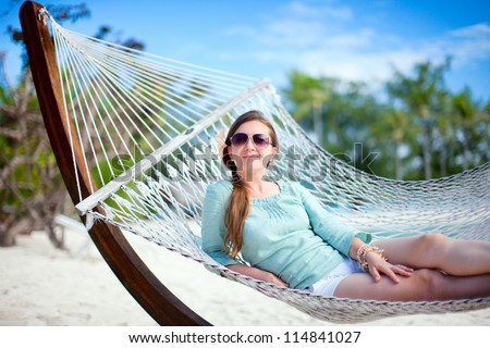 Beautiful woman relaxing at hammock on tropical beach - stock photo