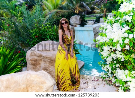 Beautiful woman relaxing by the pool - stock photo