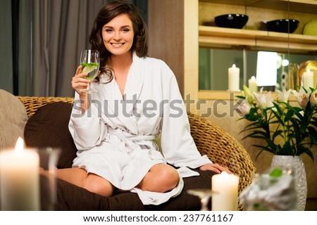 Beautiful woman relaxing in a bathrobe in spa salon  - stock photo