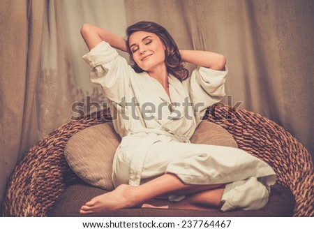 Beautiful woman relaxing in a bathrobe in spa salon  - stock photo