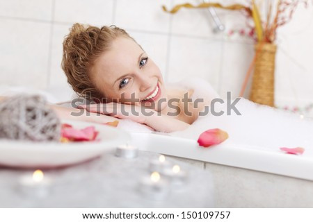 Beautiful woman relaxing in a foamy bubble bath resting her head on the side and smiling at the camera in appreciation and enjoyment - stock photo
