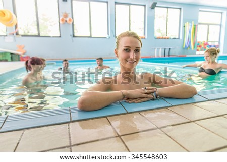 Beautiful woman relaxing in a spa - Several young and attractive people having fun and partying on summer vacation - Girl portrait in an indoor pool - stock photo