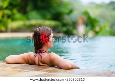 Beautiful woman relaxing in infinity swimming pool - stock photo
