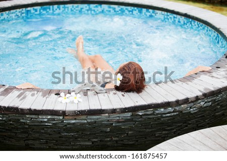 Beautiful woman relaxing in jacuzzi at spa center - stock photo