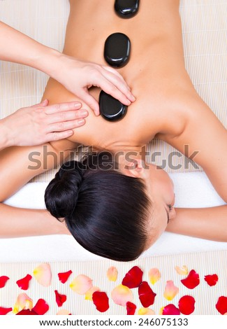 Beautiful woman relaxing in spa salon with hot stones on body. Beauty treatment therapy - stock photo
